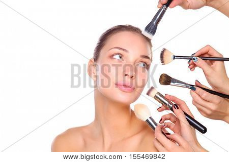 Young woman with make up brush, isolated on white background