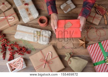 High angle shot of a man holding a Christmas Present over a table filled with wrapped gifts and wrapping supplies.