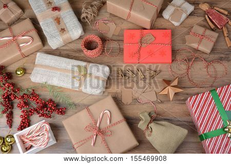 High angle shot of a table filled with wrapped Christmas gifts and wrapping supplies.