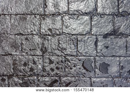 Close up texture of wet black brick wall background.