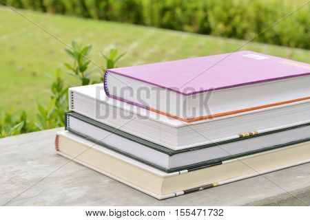 Stack of books in the green garden