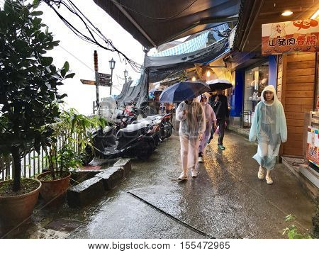 JIOUFEN - OCTOBER 29: Tourists browse the market street on a rainy day on October 29, 2016 in Jioufen, Taiwan.