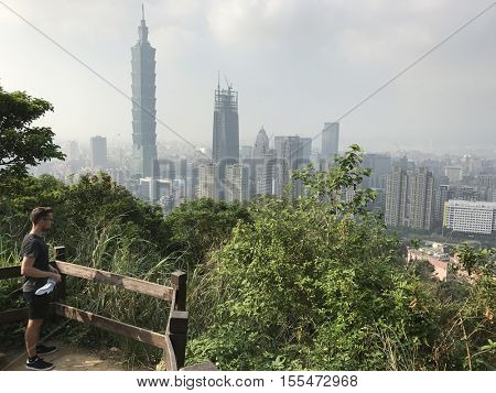 TAIPEI - OCTOBER 28: A male hiker looks out over the city skyline from a lookout on The Elephant Mountain Trail on October 28, 2016 in Taipei, Taiwan.