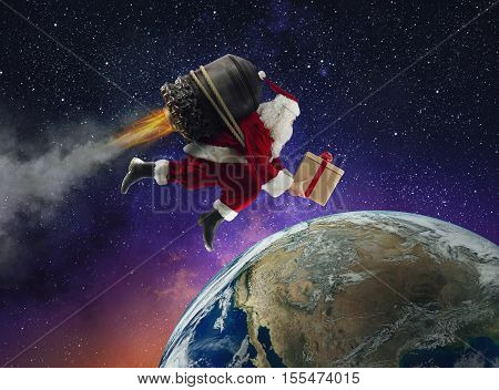 Santa Claus with gift box flies with a missile in a space