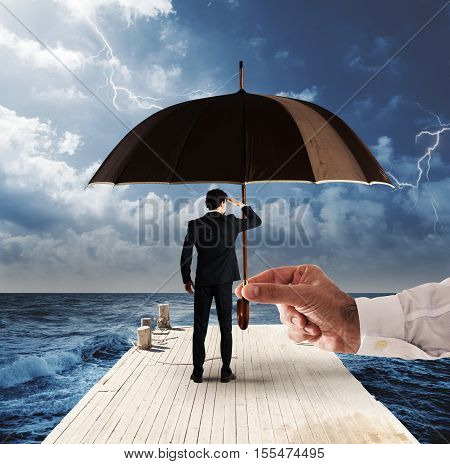 Man covered by an umbrella while watching the horizon from a pier with stormy sea