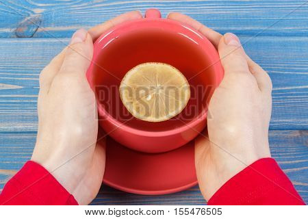 Hand Of Woman Holding Cup Of Hot Tea On Table