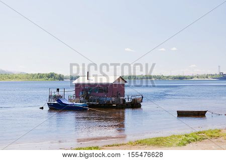 houseboat on water of river in summer surrounded by boats