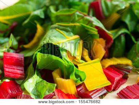 sunlight shining down on a salad of chopped red and yellow swiss chard shot with a selective focus.