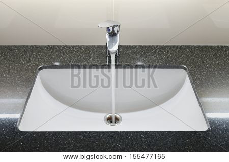 Modern style wash basin with black granite counter and faucet