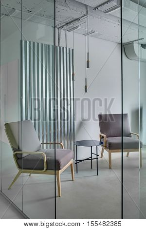 Armchairs with wooden legs and a small round metal table on the background of the gray wall with the metal panel. In front of them  there is a glass partition with an entrance. Indoors. Vertical.