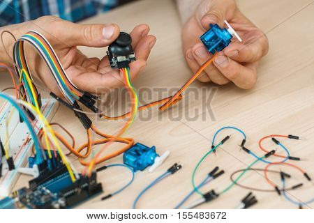 Workplace of engineer working with electronics. Close-up of programmer hands holding components in hands with a lot of colorful cables, free space
