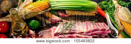 Raw Beef Ribs And Vegetables On A Dark Wooden Background.