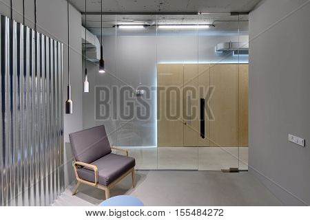 Business interior in a loft style with gray walls. There is a room with a glass partition with door, an armchair, a small table and a metal panel on the wall. Opposite the room there are wooden doors.