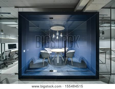 Meeting room with blue walls and furniture and a glass door in the office in a loft style with gray walls. Around it there are work zones with glass and mesh partitions. Lamps are glowing. Horizontal.