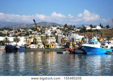 CALETA DE VELEZ, SPAIN - OCTOBER 27, 2008 - View of fishing boats moored in the harbour with town buildings to the rear Caleta de Velez Malaga Province Andalusia Spain Western Europe, October 27, 2008.