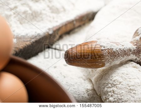Close up rolling pin with flour and eggs with copy space. Bakery background