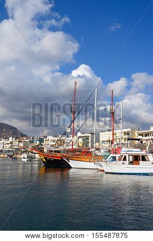HERSONISSOS, CRETE - SEPTEMBER 14, 2016 - Yachts moored in the harbour with waterfront restaurants to the rear Hersonissos Crete Europe, September 14, 2016.