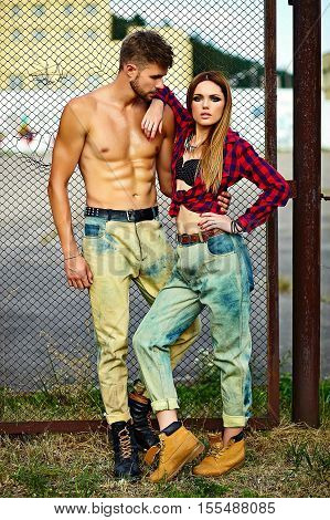 High fashion look.beautiful couple sexy stylish blond young woman model with bright makeup with perfect sunbathed skin and handsome muscled man in vogue style in jeans outdoors