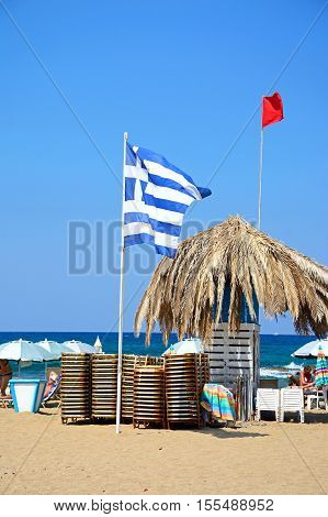 MALIA, CRETE - SEPTEMBER 14, 2016 - Flags sun loungers and a large parasol on Potamos beach with the sea to the rear Malia Crete Greece Europe, September 14, 2016.