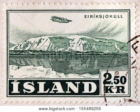 LUGA RUSSIA - NOVEMBER 6 2016: A stamp printed by ICELAND shows Aircraft over Eiriksjokull (Eiriks glacier) - famous glacier north-west of Langjokull in Iceland circa 1952