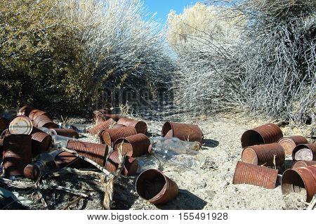 Old, discarded cans and glass bottles in the desert