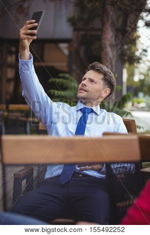 Businessman taking selfie at outdoor café
