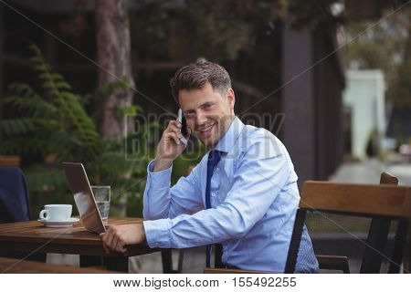 Handsome businessman talking on mobile phone while using laptop at outdoor cafe