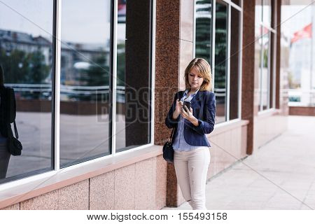 Young woman using smart phone while standing near building.