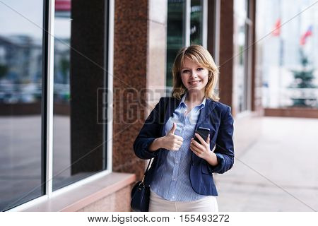 Young woman using smart phone and showing thuambs up gesture while standing near building.