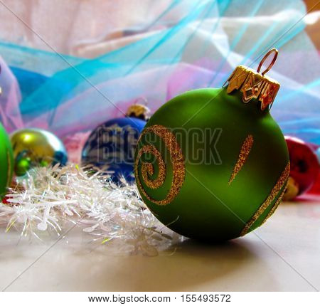 Green ball on Christmas tree. Beautiful festive greeting card with colorful balloons and décor