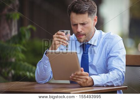 Businessman having drink while using digital tablet at outdoor cafe