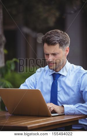 Handsome businessman using laptop at outdoor cafe