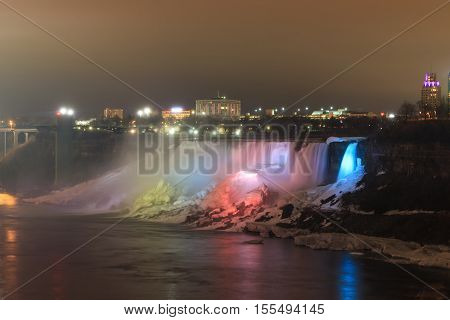 Niagara Falls lit at night by colorful lights between the Canadian province of Ontario and the U.S. state of New York.