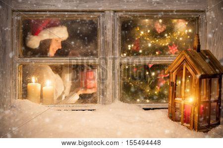 Atmospheric Christmas window with Santa girl holding gift next to christmas tree