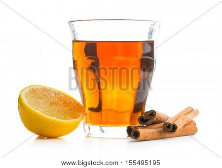 Tea in glass cup, lemon and cinnamon sticks isolated on white background.