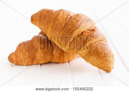 Two buttery croissants on white table.