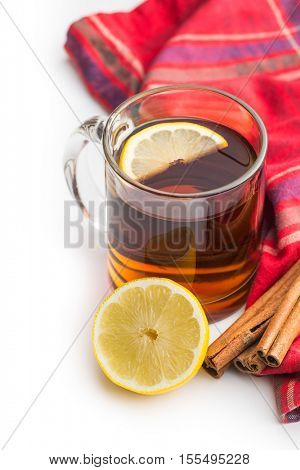 Tea in glass cup with sliced lemon, cinnamon sticks and napkin isolated on white background.