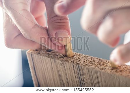 Man assembling furniture at home male hand with wooden dowel pins and plywood board