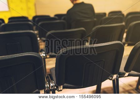 Unrecognizable journalist in press conference room sitting alone among empty chairs selective focus