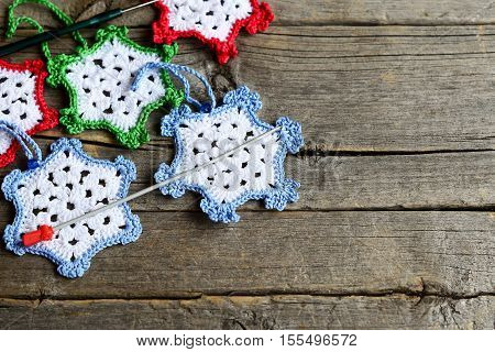 Crocheted snowflakes, two hooks on an old wooden background with blank copy space for text. Simple winter crafts for kids and beginners. Crochet home decorations