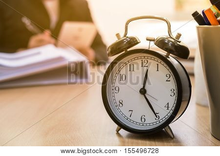 alarm clock on the table in office over time concept