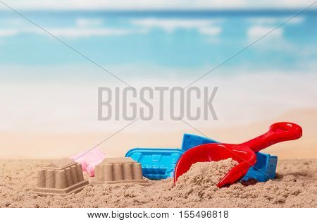 Bright children's toys in the sand against the sea.