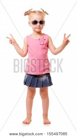 Little blonde girl in sunglasses shows a victory sign isolated on white background.