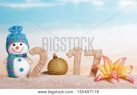 Christmas ball instead of the number 0 in the amount of 2017 snowman and flower in the sand against the sea.