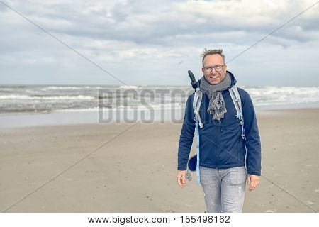 Man Walking Along A Cold Blustery Beach