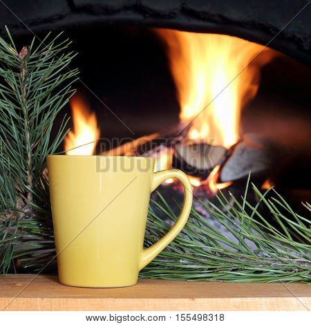 yellow mug on the background of pine branches and of melted the home fireplace / vacation in the warming atmosphere