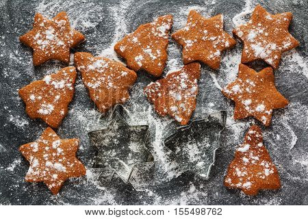 Christmas chocolate and ginger brown cookies in shape of fir-tree and star on black stone background with powdered sugar top view.