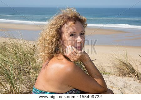 Beautiful Woman Looking Away While Sitting At Beach