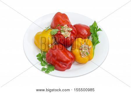 Several cooked stuffed red and yellow bell peppers and twigs of parsley and cilantro on a white dish on a light background