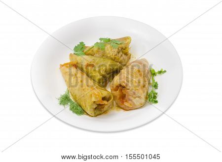 Several cooked cabbage rolls twigs of parsley dill and cilantro on white dish on a light background